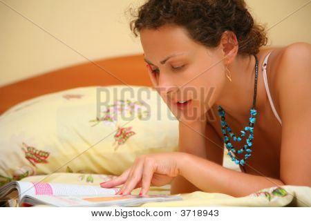 Young Woman Reads On Bed