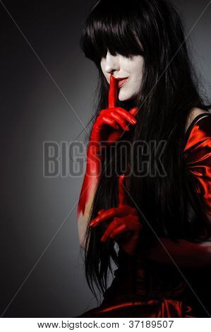 Young mysterious fashion witch vampire with finger on the lips against the dark background