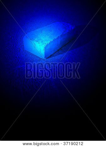 Luz azul mágico sobre tijolo com silhueta no asfalto, desconhecida da ciência