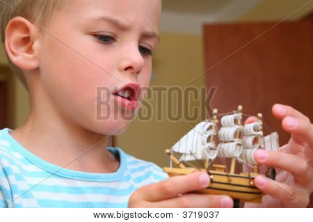 Boy With Model Of Ship In Hands