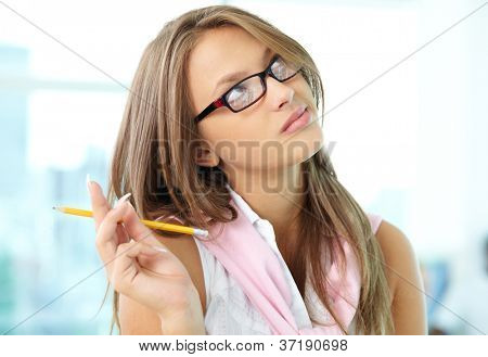 Portrait of pensive girl in eyeglasses holding pencil