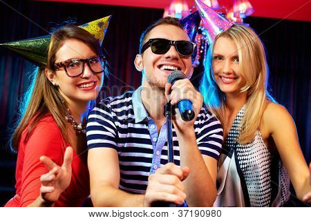 Portrait of happy friends singing in microphone in the karaoke bar