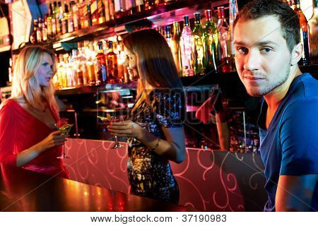 Portrait cute guy looking at camera at party with two girls chatting on background