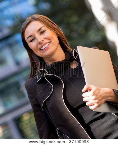 Mujer de negocios llevar un ordenador portátil en la ciudad