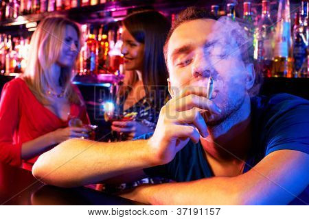 Portrait of young man smoking in the bar with two girls on background