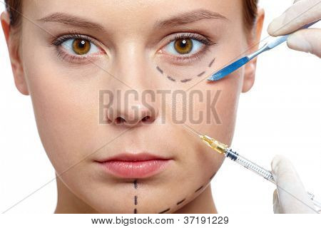 Fresh woman with marks drawn on face during procedure