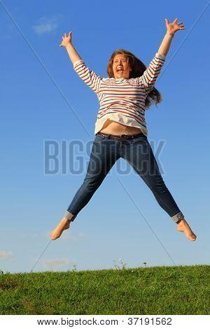 Jovem jeans pula e grita em grama verde no fundo do céu azul.