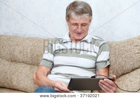 Senior Adult Caucasian Man Interested With A New Tablet Computer, Sitting On Sofa In Domestic Room