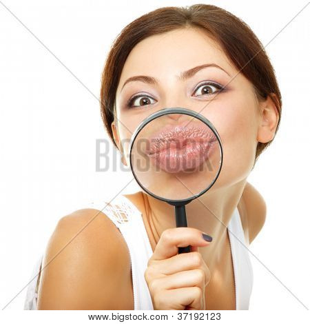attractive young woman give kiss through a magnifying glass over white background