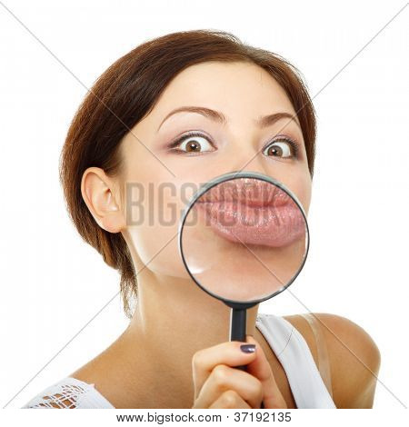 funny woman looking through a magnifying glass over white background