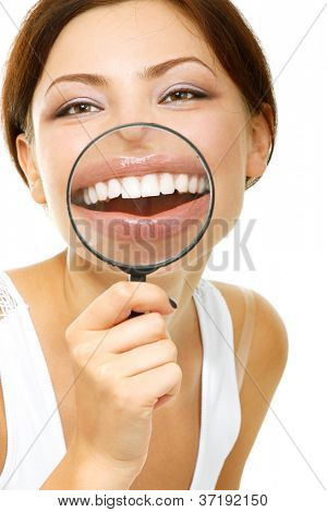 funny woman smiling and show teeth through a magnifying glass over white background