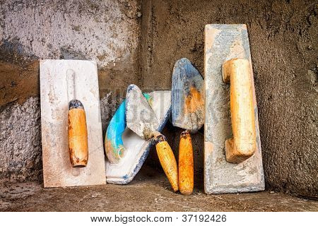 Set of masonry tools on a rough unfinished concrete surface