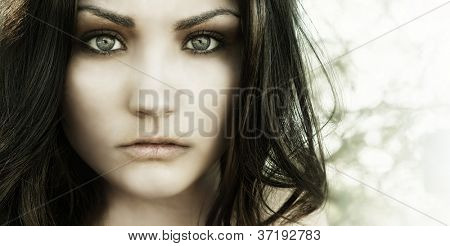 Close up photo of beautiful young woman's face with big eyes and vacant eerie stare.