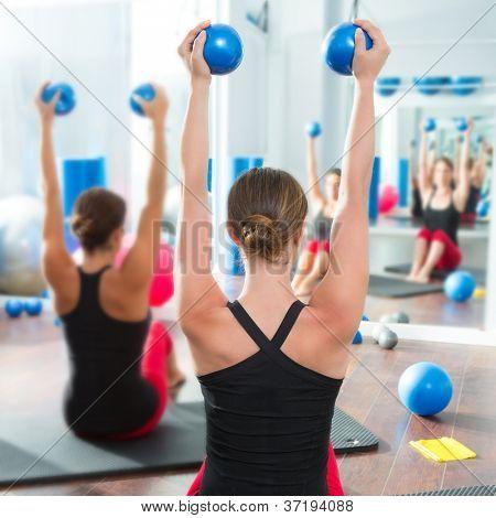 Pilates toning ball in women fitness class rear mirror view