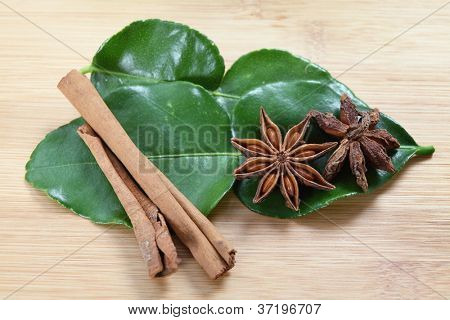 Star anise (Illicium verum - both sides of the pod shown), cinnamon and kaffir lime  (Citrus hystrix) leaves on a chopping board, these are all ingredients in Asian cookery.