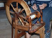stock photo of handloom  - Antique vintage spinning wheel loom with a weaver at work.