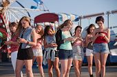 stock photo of amusement  - Group of 8 teenage girls text messaging at an amusement park - JPG
