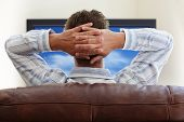 Man sitting on a sofa watching tv with hands folded behind his head