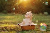 foto of wash-basin  - the kid outdoors bathes in a basin in the summer on a green grass - JPG