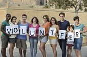 foto of diversity  - happy and diverse volunteer group holding sign - JPG