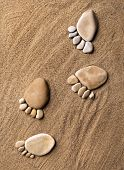 trace feet steps of a pebble stone walking on the sea sand backdrop