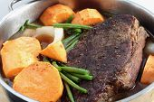 A traditional American pot-roast with beef, gravy, onion, sweet potato and green beans. This is at t