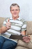Senior Caucasian Man And Tablet Pc  Thumb Is Up.  Domestic Room, Sofa poster