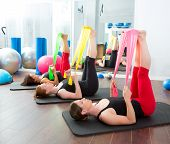 foto of rubber band  - Aerobics pilates women group with rubber bands in a row at fitness gym - JPG