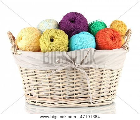 Colorful yarn balls in wicker basket isolated on white