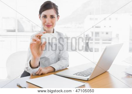 Happy businesswoman showing blank business card at her desk with laptop