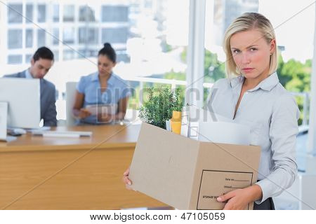 Businesswoman leaving office after being laid off and looking at camera carrying box