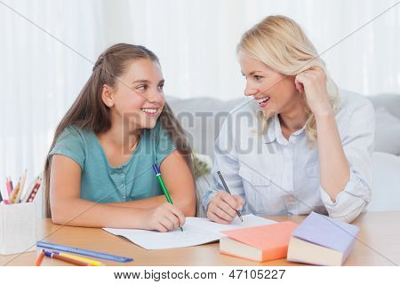 Cheerful mother and daughter writing together in the living room