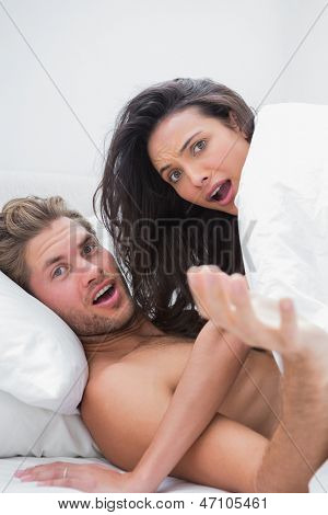 Embarrassed couple surprised in their bed