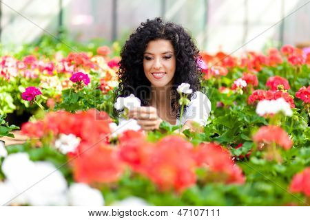 Young woman looking at flowers in a greenhouse