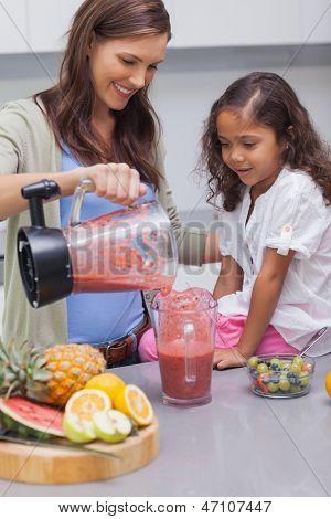 Frau gießt Frucht von einem Mixer in Tasse