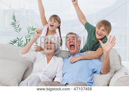 Grandparents and grandchildren raising arms in the living room