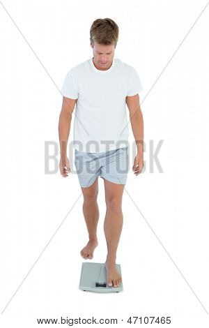 Handsome man getting on a weighing scale on white background