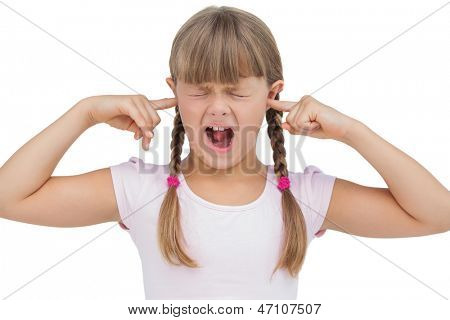 Funny little girl clogging her ears and wincing on white background