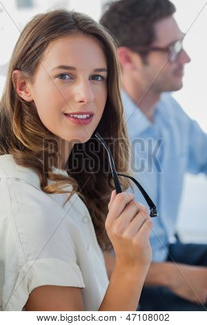 Smiling photo editor holding her reading glasses next to a colleague