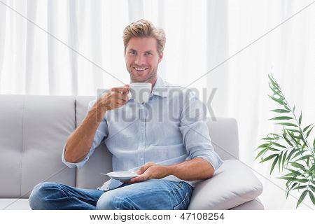 Man sitting on his couch drinking a coffee in the living room