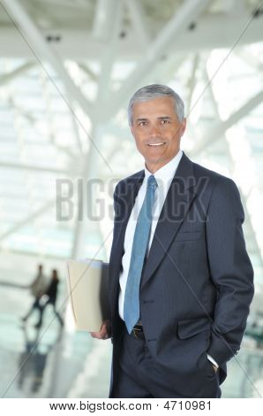 Middle Aged Businessman In Lobby With Folder