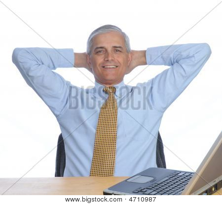 Middle Aged Man At Desk With Hands Behind His Head