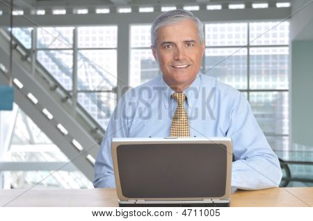 Middle Aged Businessman With Laptop Computer At Dest