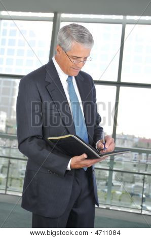 Middle Aged Businessman Taking Notes