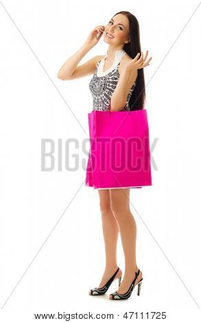 Young girl with bags talking by mobile phone isolated