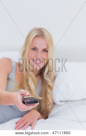 Blonde woman pointing the remote control at the camera in her bed