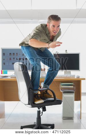 Handsome man surfing his office chair and having fun
