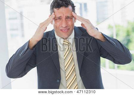 Businessman rubbing his temples and frowning at camera in office