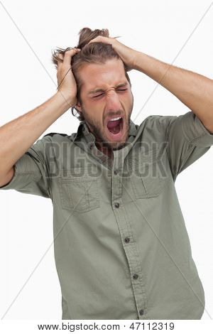 Sleepy man yawning and running fingers through hair on white background