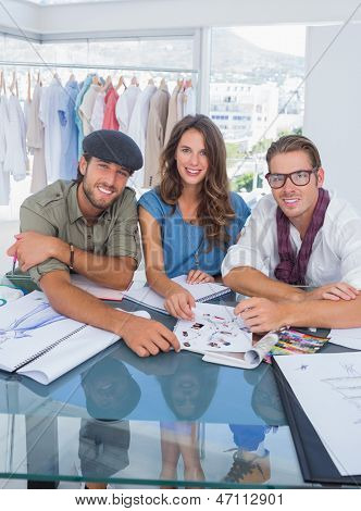 Smiling fashion designers smiling at camera in a bright office